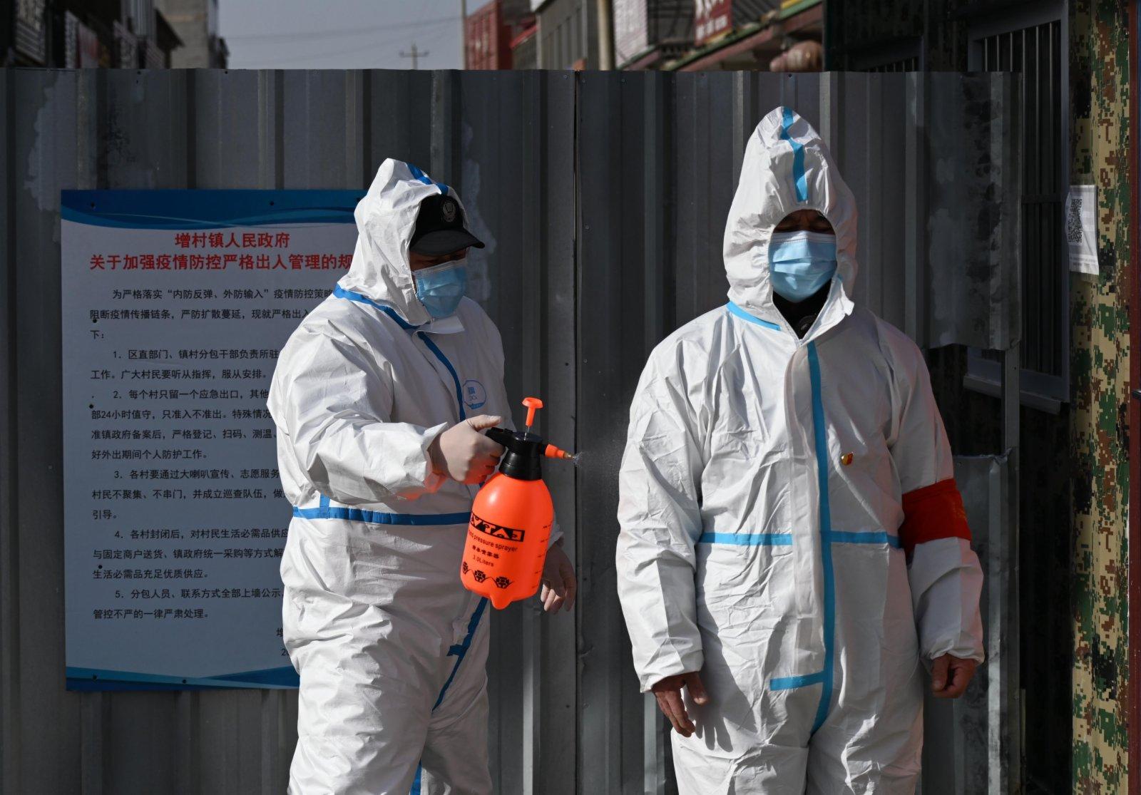 警員為從小果莊村出來的防疫工作人員消毒。中新社