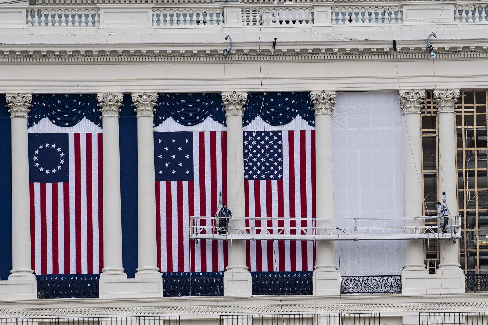 1月11日,在美國首都華盛頓,工作人員在國會大廈外懸挂旗幟,為下屆總統的就職典禮做準備。(新華社)