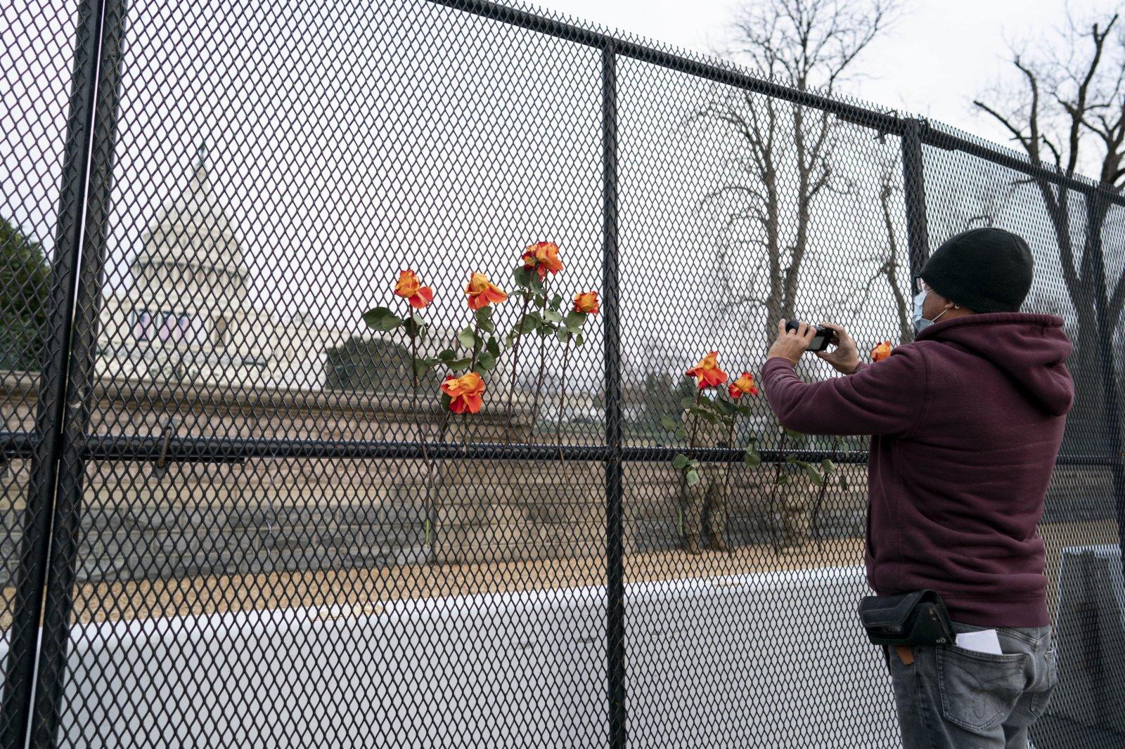 1月11日,在美國首都華盛頓,一名男子在國會大廈附近的隔離圍欄外拍照。(新華社)