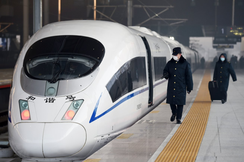 1月22日,在停靠于哈爾濱西站的京哈高鐵G902次列車旁,工作人員在進行檢查。(新華社)