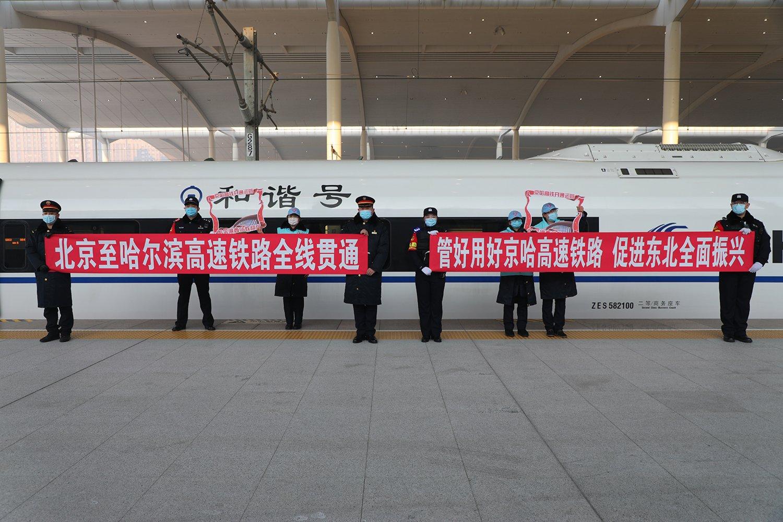 1月22日,在停靠于哈爾濱西站的京哈高鐵G902次列車旁,工作人員和志願者在留影。(香港文匯網記者 於海江 攝)