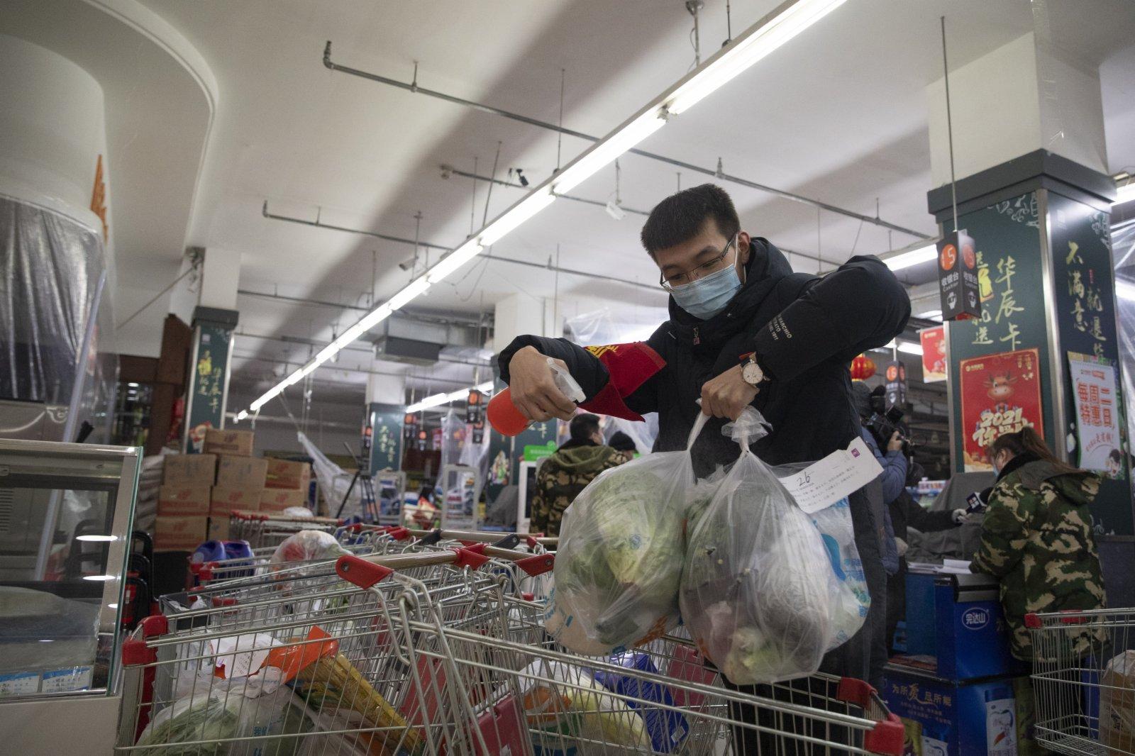 1月22日,工作人員在綏化市華辰超市對準備配送的物資進行消殺。(新華社)