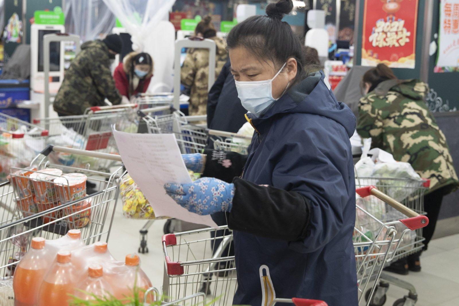 1月22日,工作人員在綏化市華辰超市按照市民訂單準備商品。(新華社)