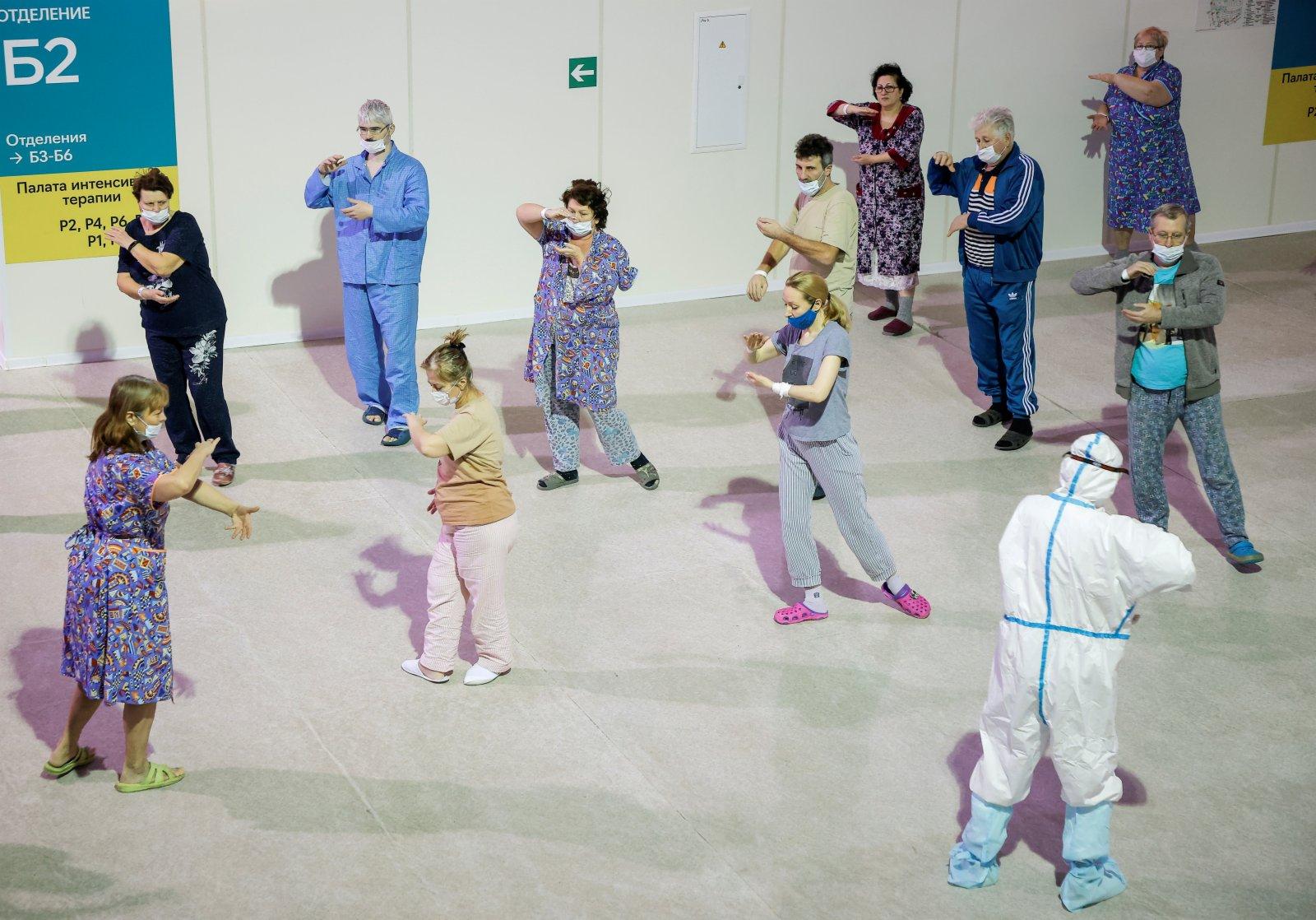 當地時間21日,莫斯科,由克雷拉茨科耶冰宮改建的臨時醫院裏,醫生帶領新冠肺炎患者打太極拳。(路透社)