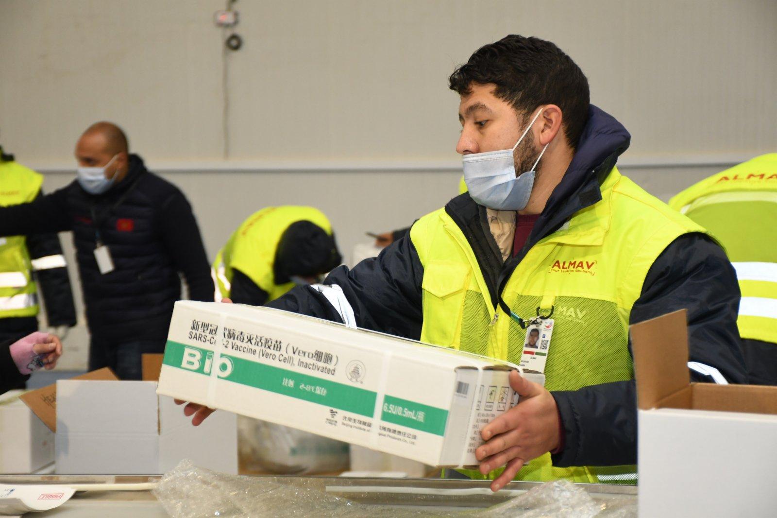 1月27日,在摩洛哥卡薩布蘭卡,工作人員搬運剛剛運抵的中國新冠疫苗。