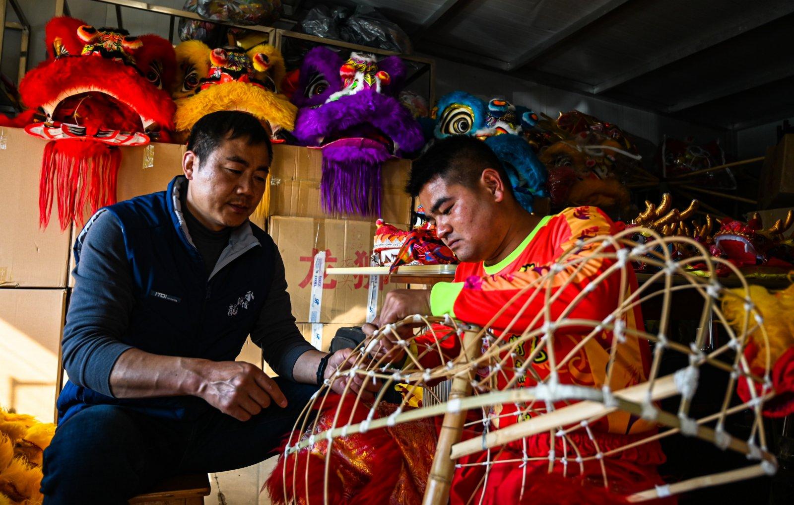 2月3日,畢付華(左)在向學生傳授彩扎技術。(新華社)