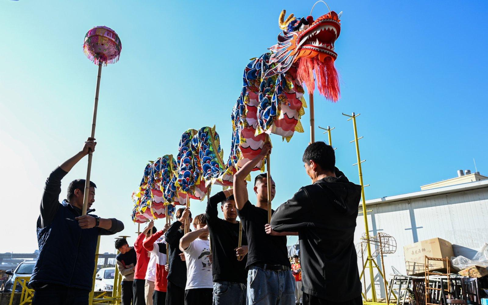 2月3日,畢付華(左一)在指導學生練習舞龍。(新華社)