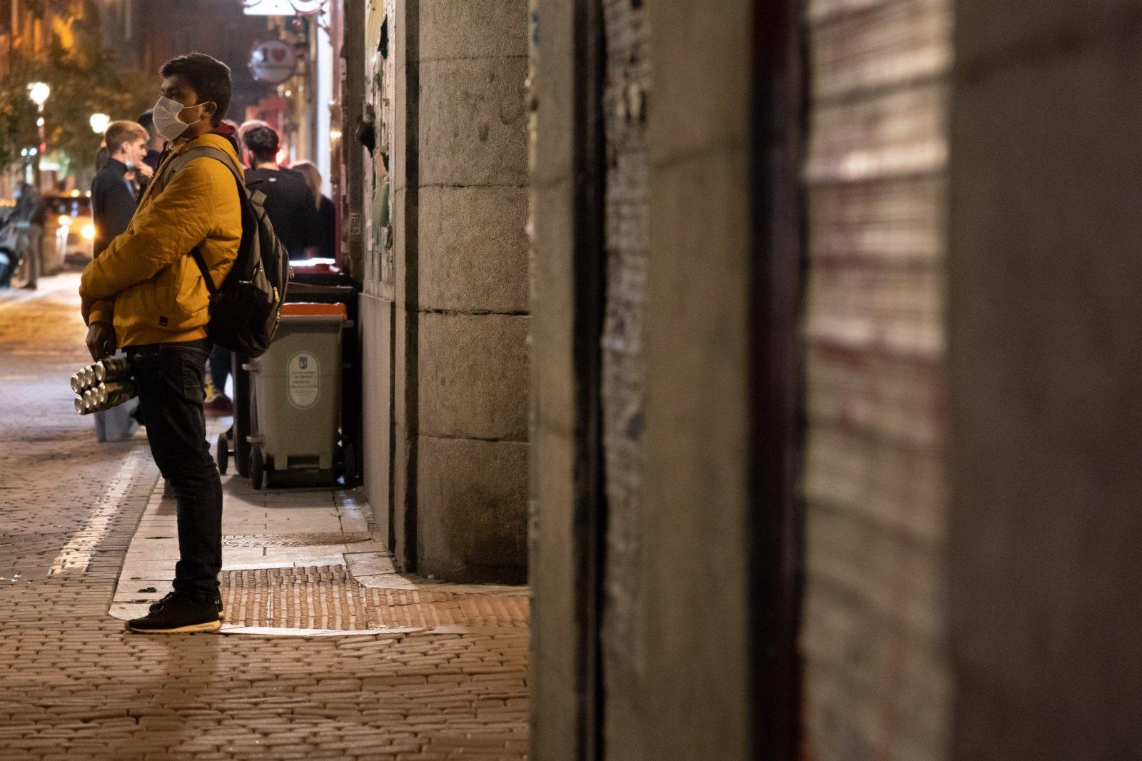 2月4日,一名佩戴口罩的男子站在西班牙馬德里街頭。(新華社)