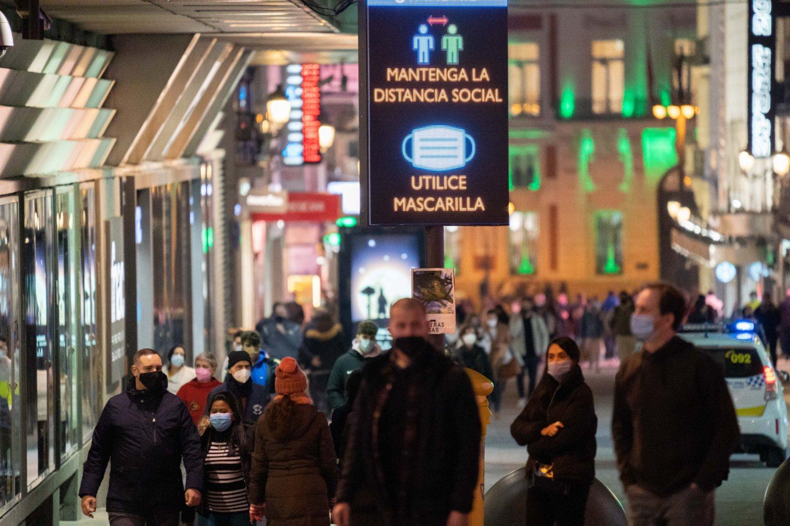 2月4日,佩戴口罩的市民走過西班牙馬德里卡利亞奧廣場。(新華社)