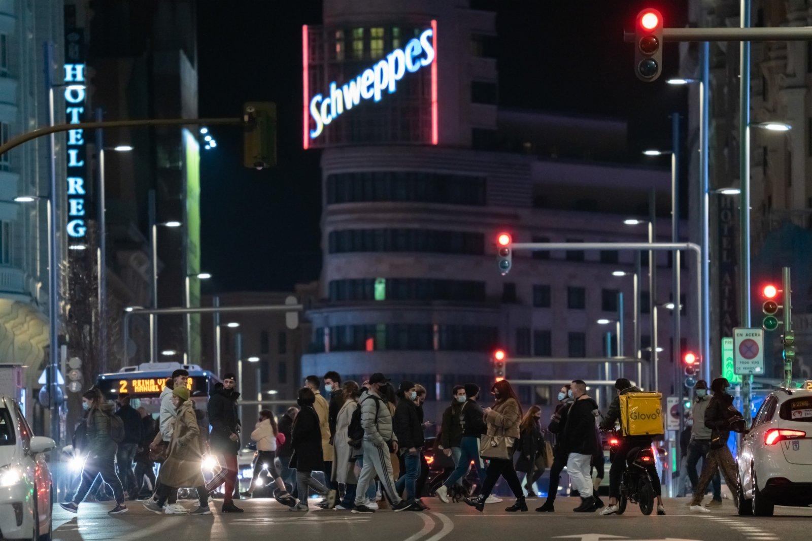 2月4日,佩戴口罩的市民走過西班牙馬德里格蘭維亞大街。(新華社)