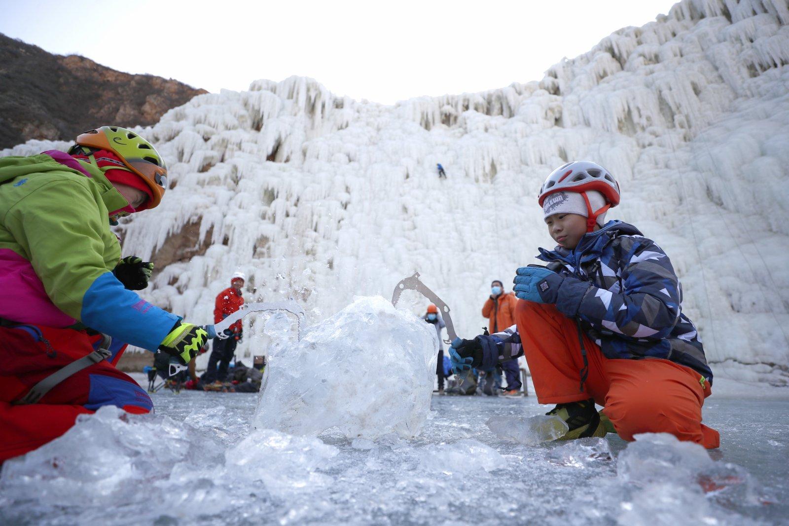 2月6日,攀冰愛好者在北京昌平區虎峪風景區攀冰場感受冰雪運動的快樂。圖為小朋友練習冰鎬使用技巧。(中新社)