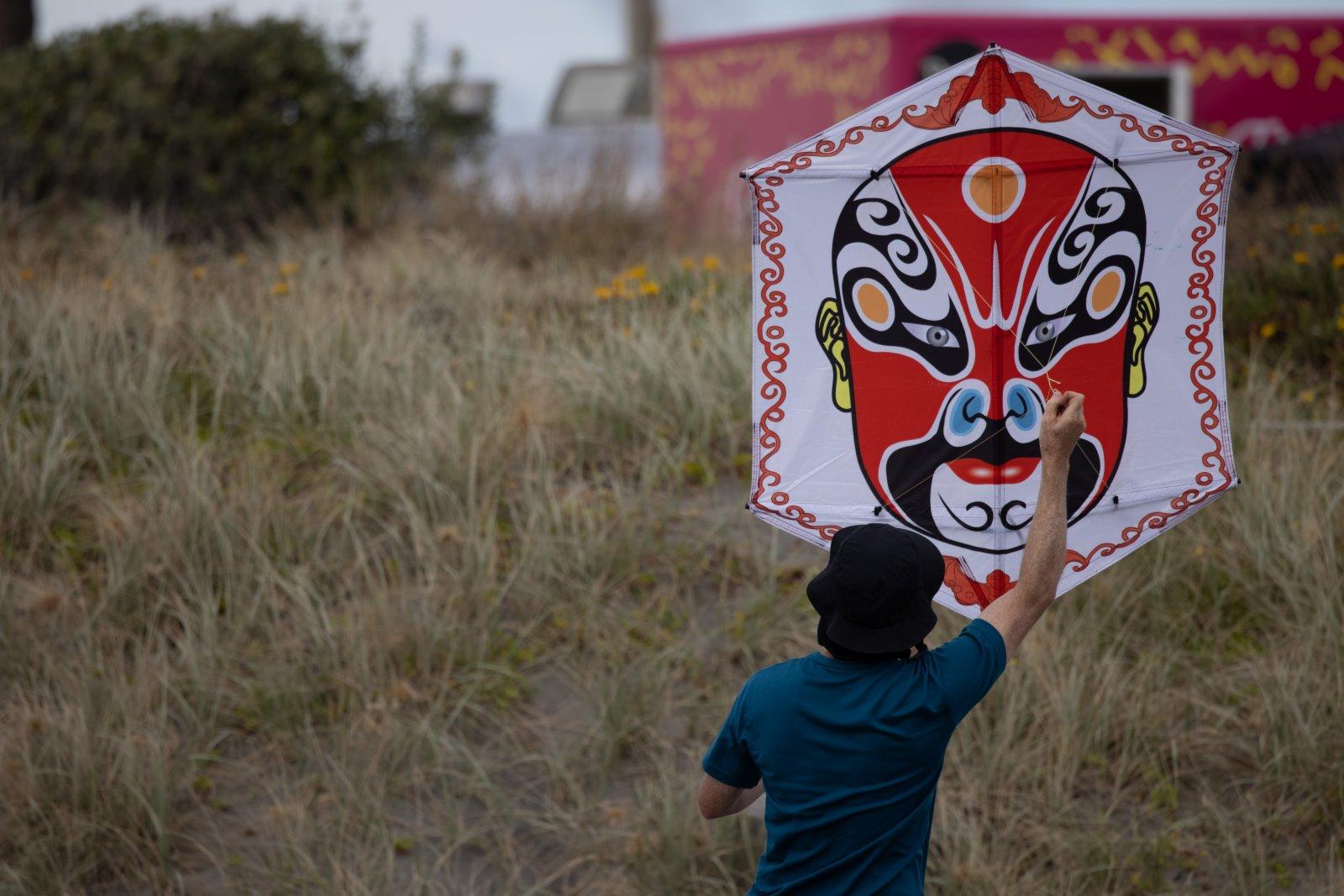 在新西蘭惠靈頓北部小鎮奧塔基的海灘上,一名男子準備放飛京劇臉譜元素風箏。