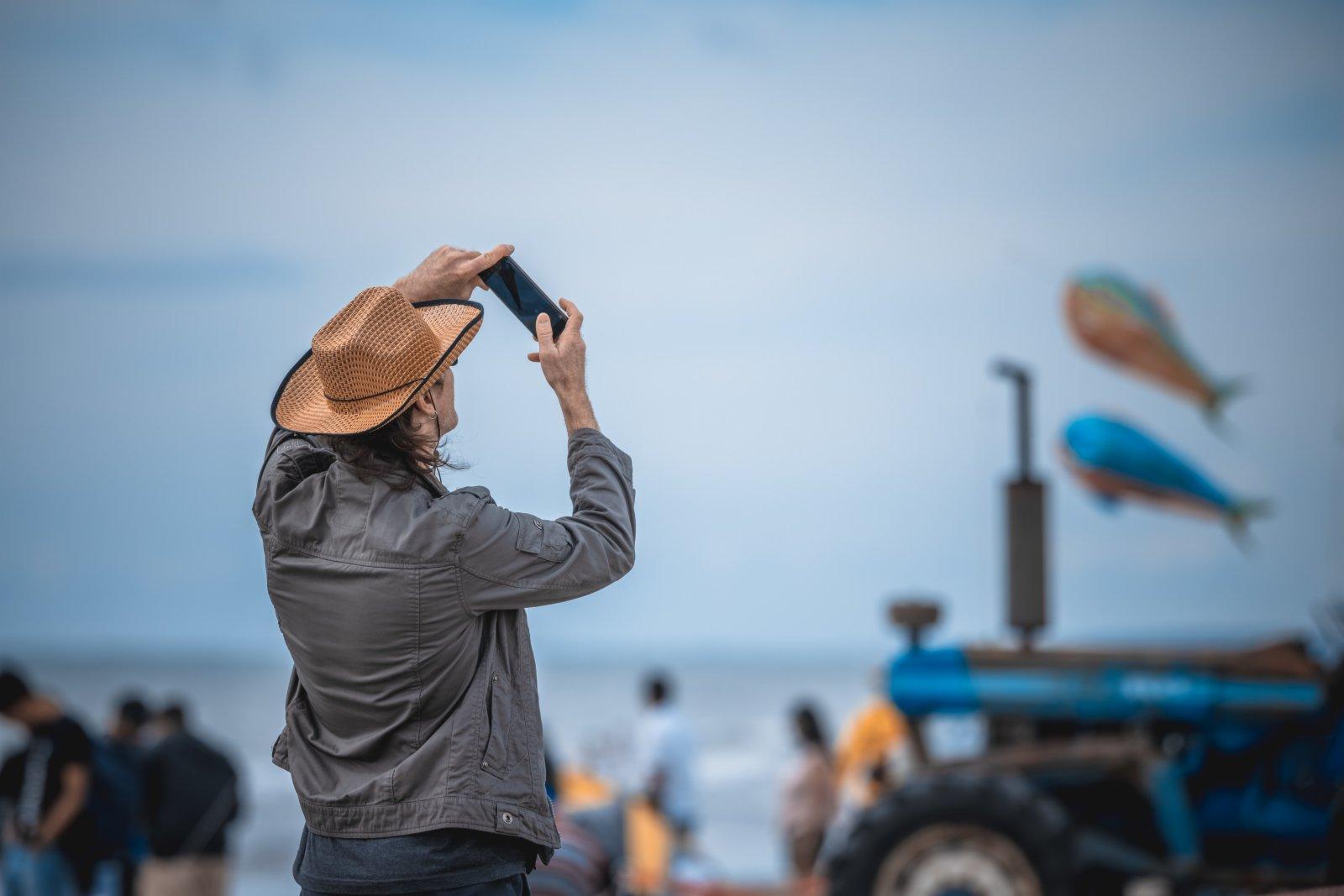 在新西蘭惠靈頓北部小鎮奧塔基的海灘上,一名觀眾在拍攝風箏。