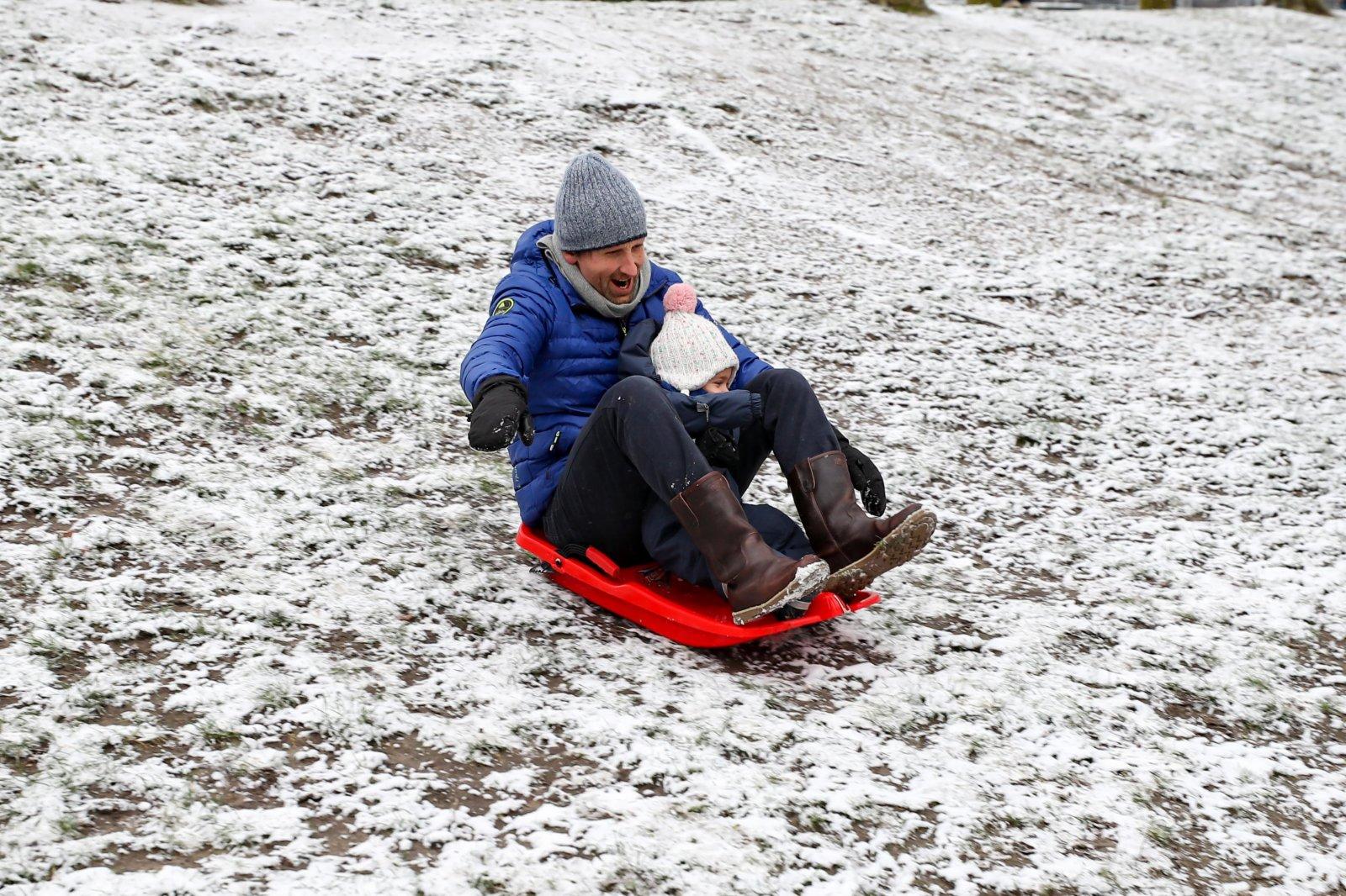 人們在比利時布魯塞爾的五十週年紀念公園玩雪。