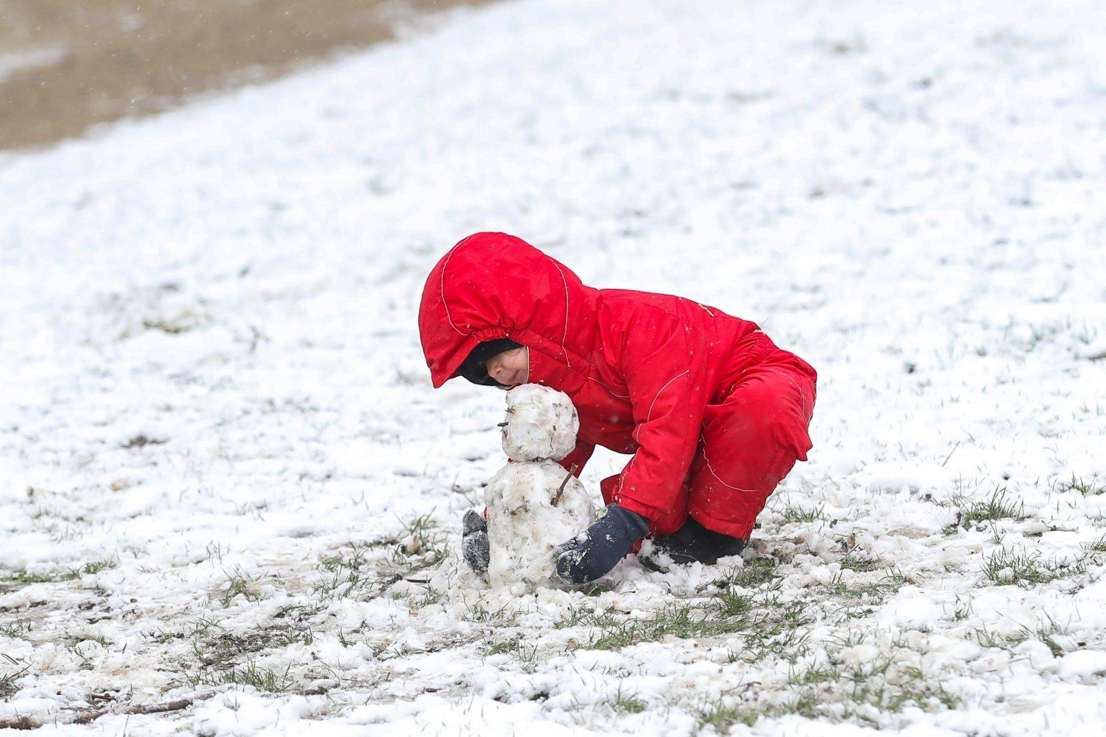 一名兒童在比利時布魯塞爾的五十週年紀念公園玩雪。