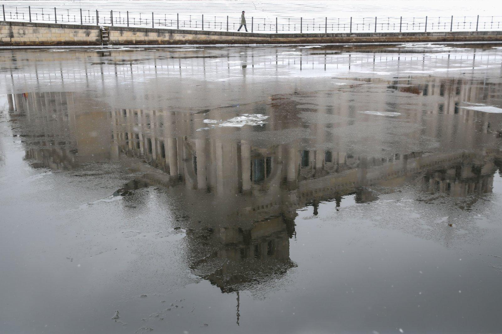 2月9日,在德國首都柏林,德國國會大廈倒映在漂有浮冰的施普雷河上。(新華社)