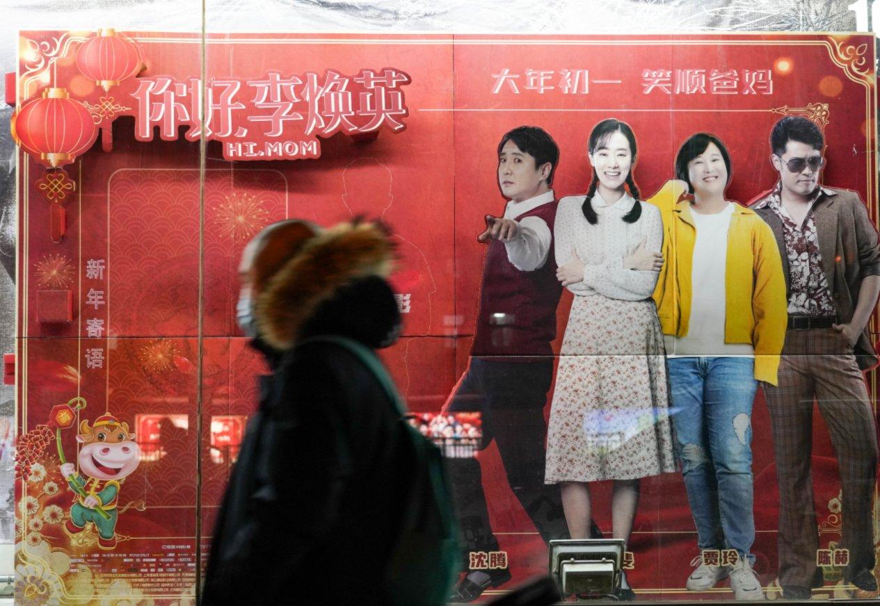 2月17日,在北京的中影國際影城外,市民從電影《你好,李煥英》海報前走過。(新華社)