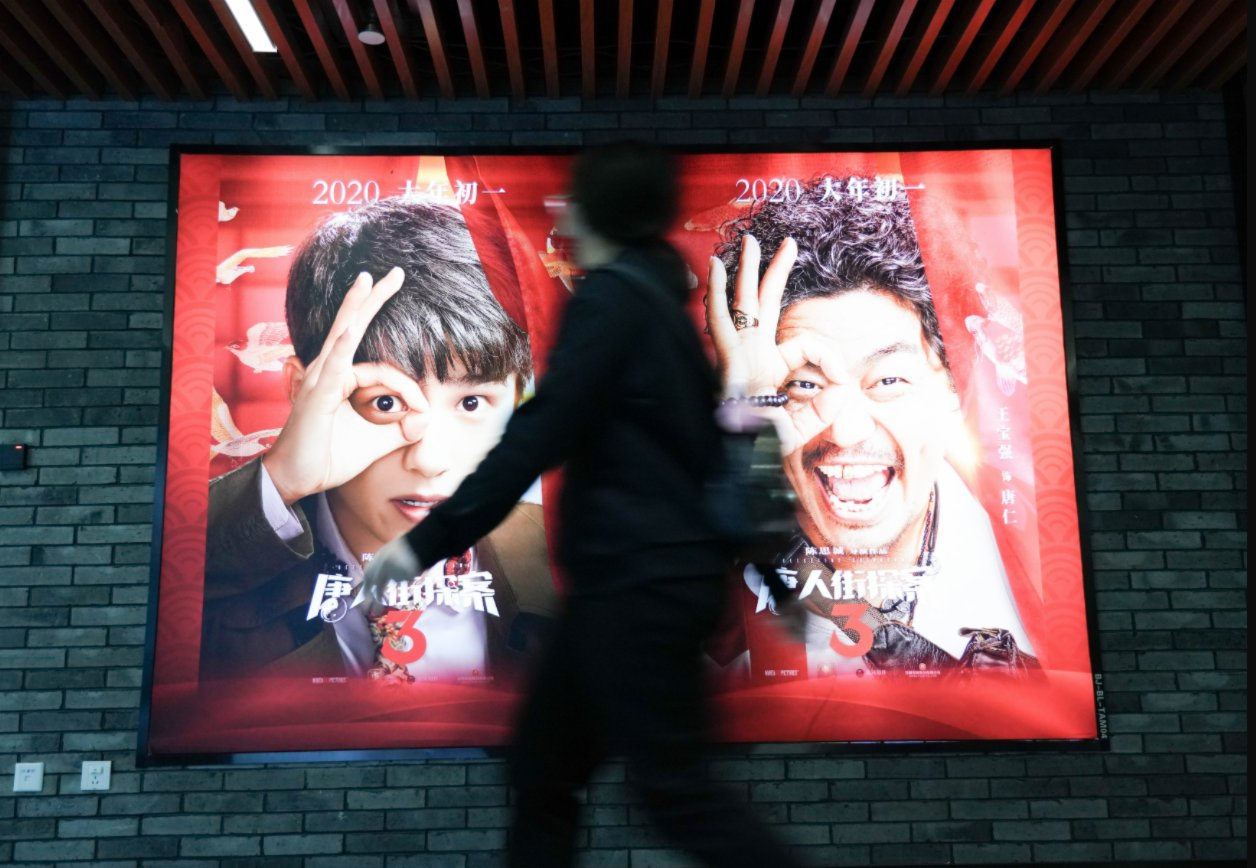 2月17日,在北京前門的保利國際影城,觀眾從《唐人街探案3》海報前走過。(新華社)