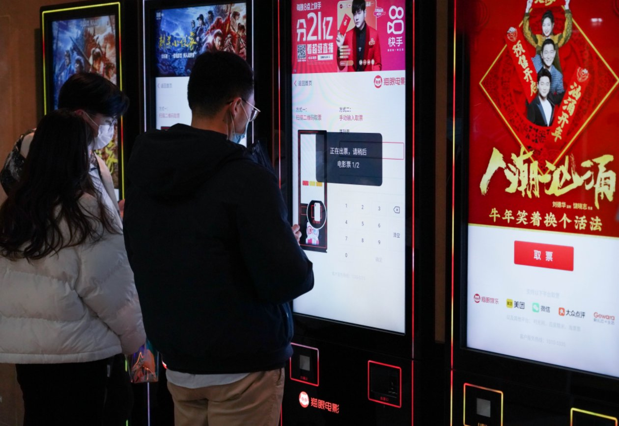 2月17日,觀眾在北京王府井的橫店電影城自助取票機前取票。(新華社)