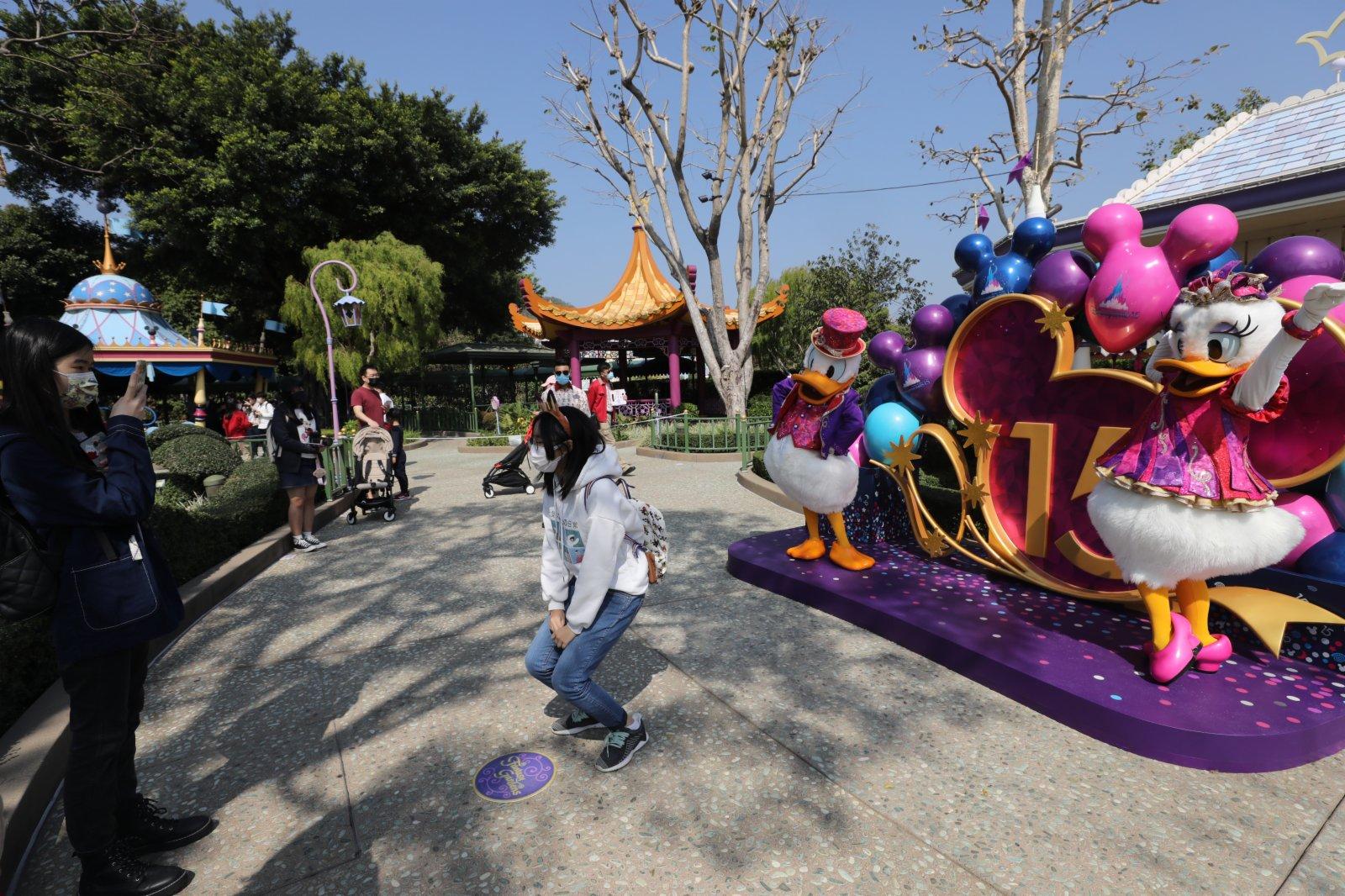香港迪士尼樂園今日(19日)重開,市民需提前預約入園。園方加強防疫措施,在入口多處展示「安心出行」二維碼,不少市民都自覺掃描。有市民表示,擔心樂園隨時再因疫情嚴重而關閉,已經預約下周再次入園。亦有市民指,以往樂園太多遊客,現時園內空間較為寬鬆,加上足足一年沒有外出旅行,因此前來放鬆。還有中六學生指,迪士尼陪伴他成長,對重開感到興奮。(香港文匯報記者萬霜靈攝)