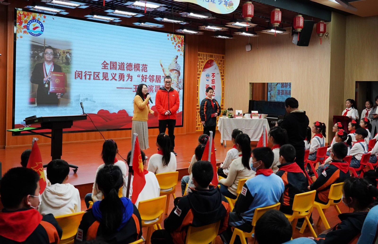 3月1日,王海濱(中)在活動現場與學生互動。(新華社)
