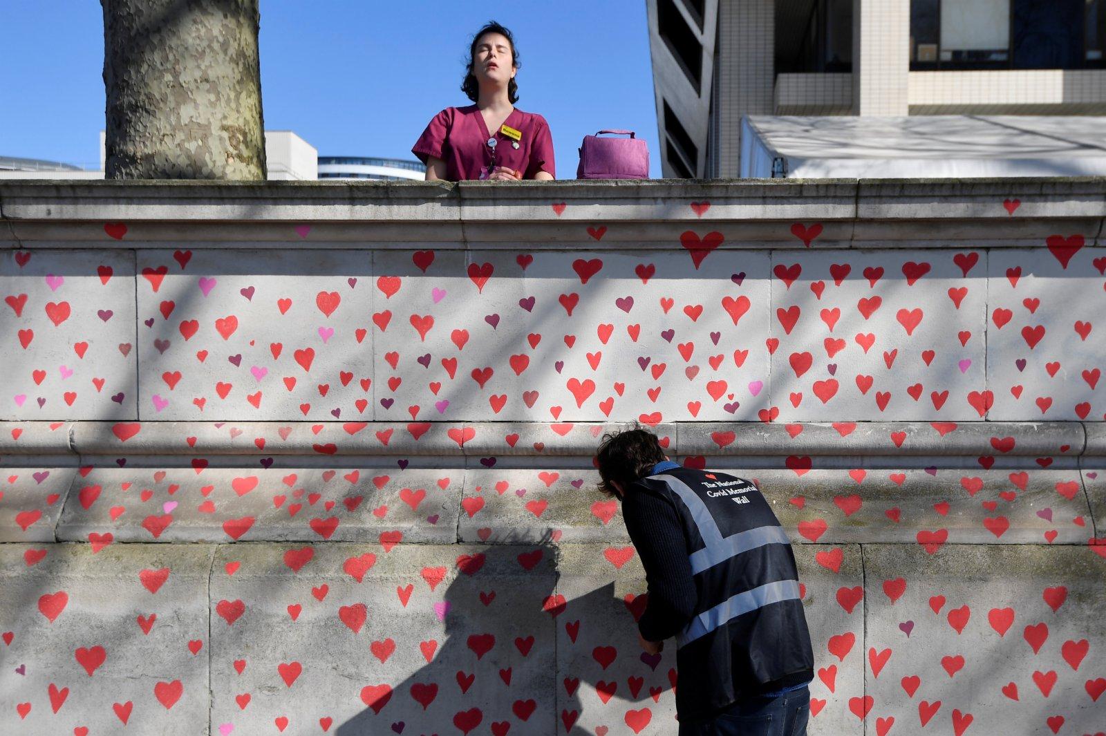 志願者和新冠疫情死難者家在繪製圖案。
