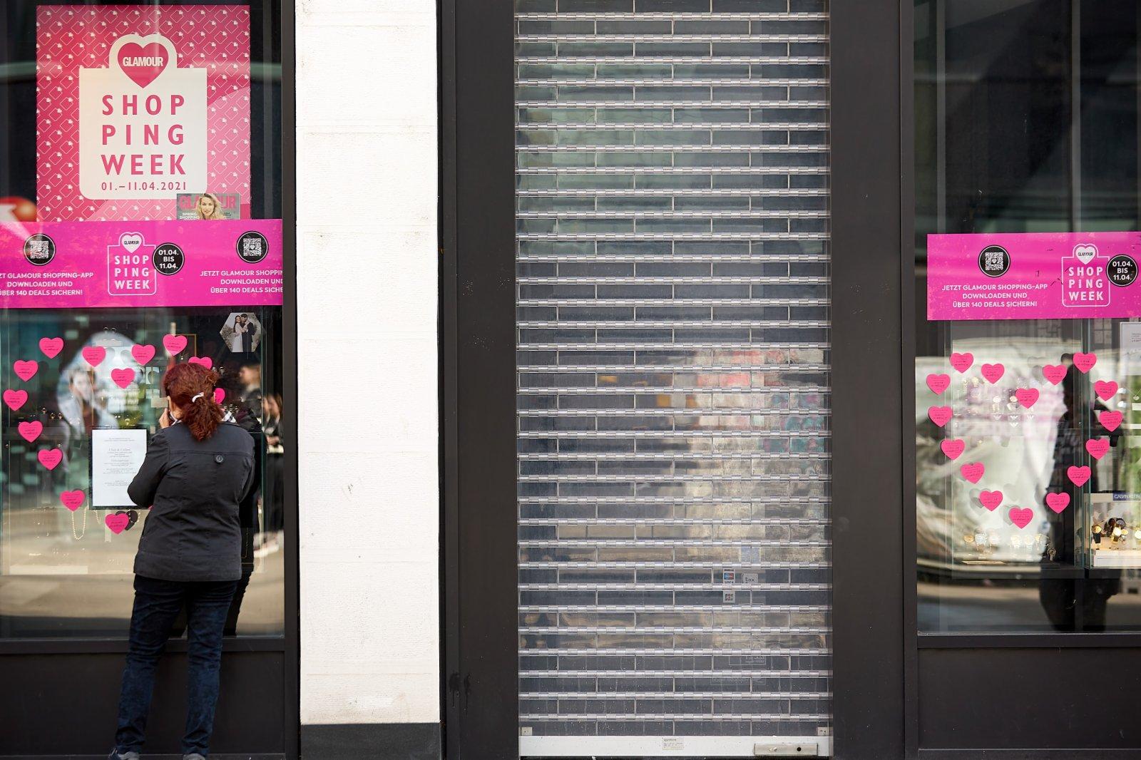 4月1日,在奧地利維也納,一名行人站在一家關閉的商店外。(新華社)
