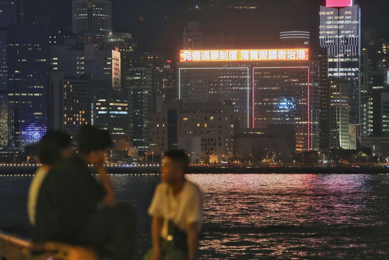 有大廈樓頂大屏幕循環播放「完善選舉制度 落實愛國者治港」的標語。香港中通社