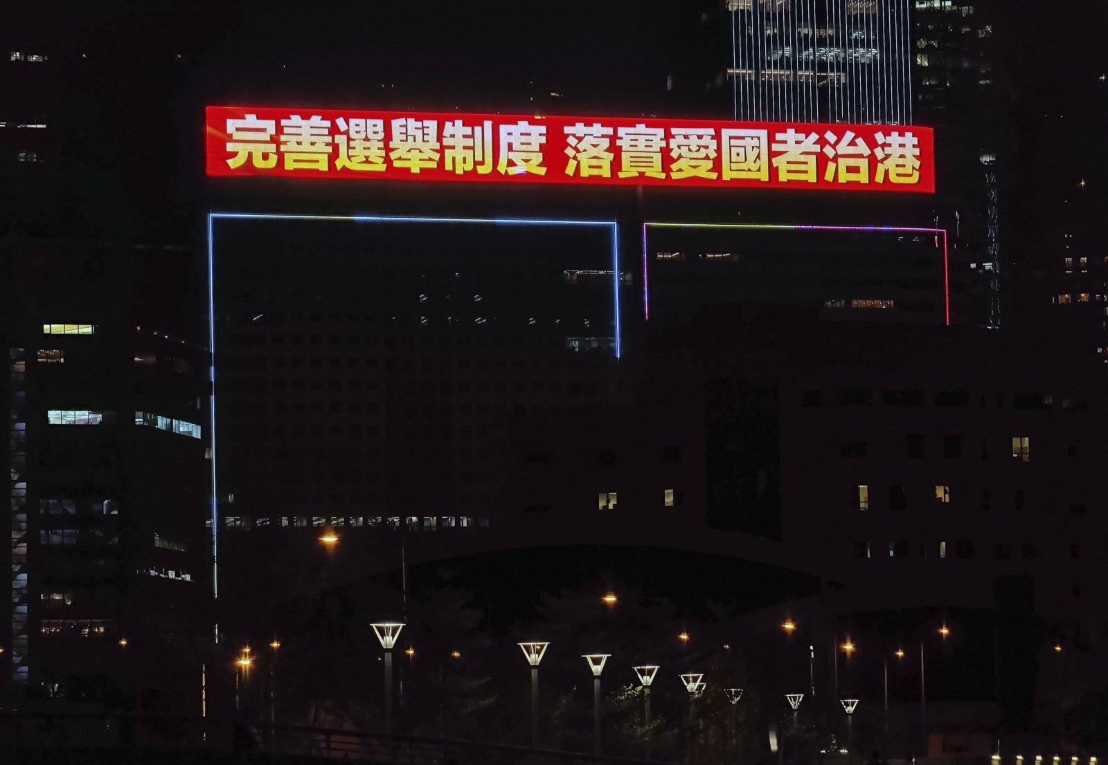 連日來,維港兩岸眾多戶外顯示屏循環播放「完善選舉制度 落實愛國者治港」的標語。 中新社