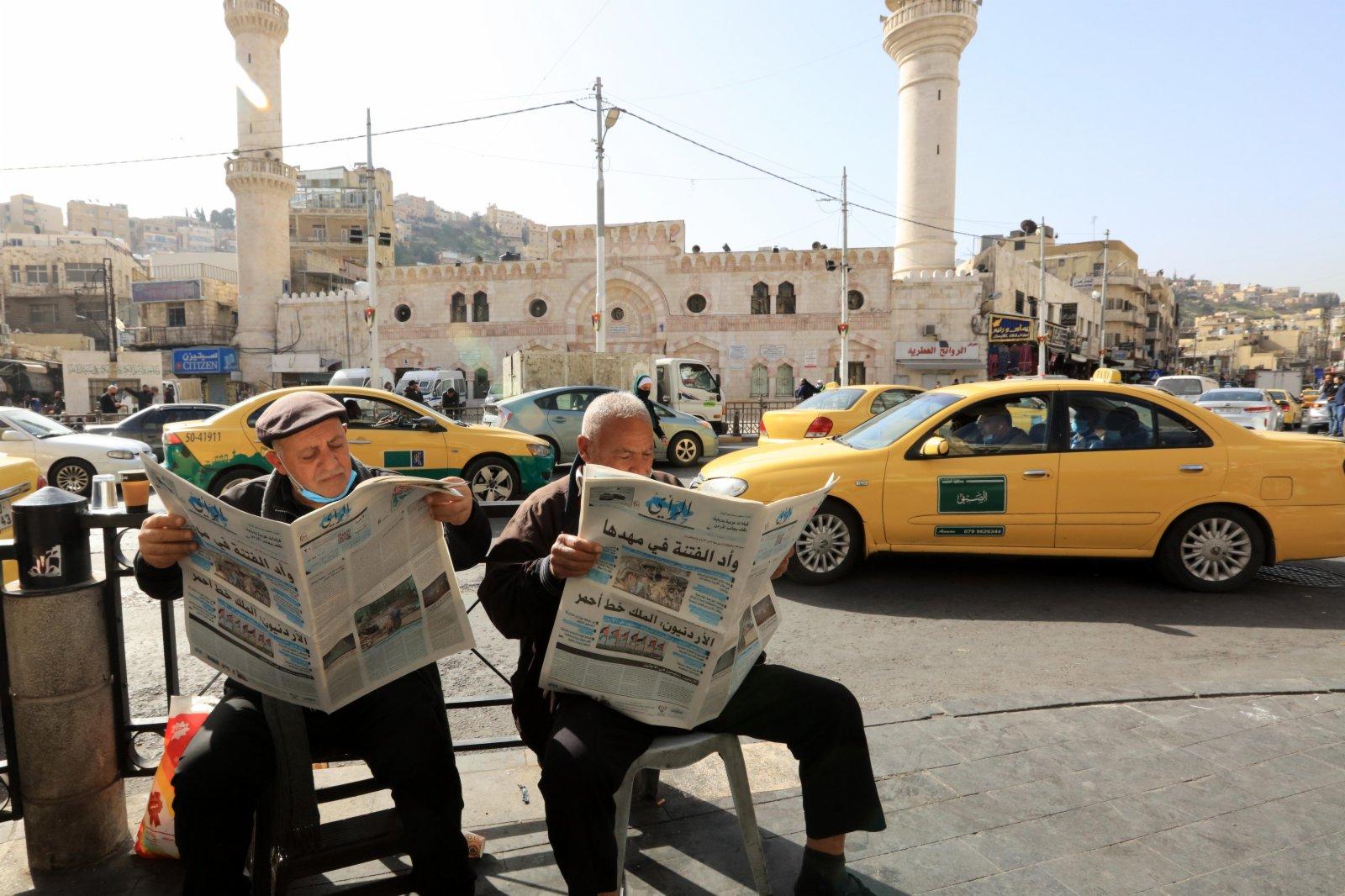 4月5日,人們在約旦安曼街頭閱讀報紙。(新華社)
