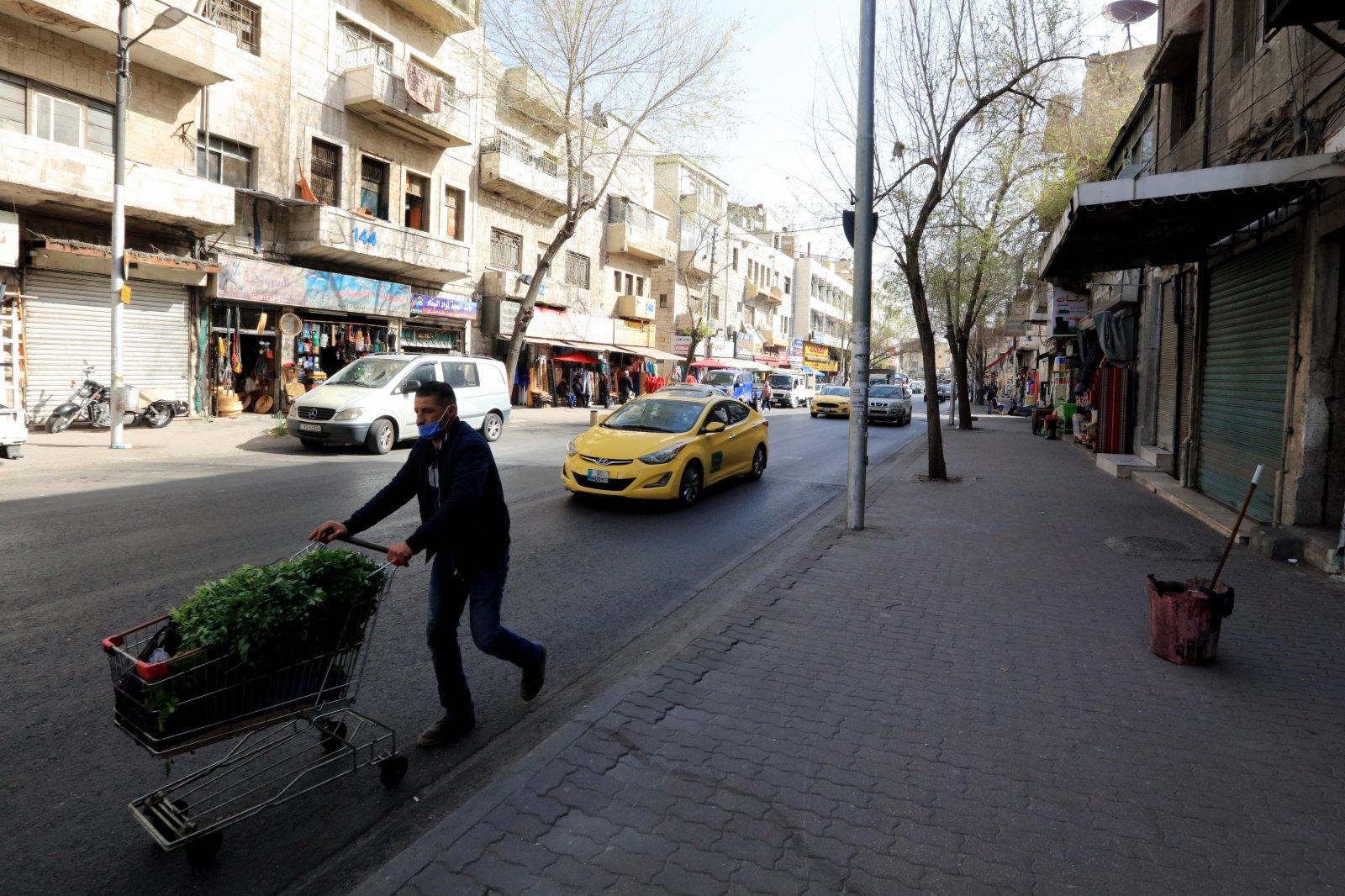 4月5日,一名男子佩戴口罩走過約旦安曼的街道。(新華社)
