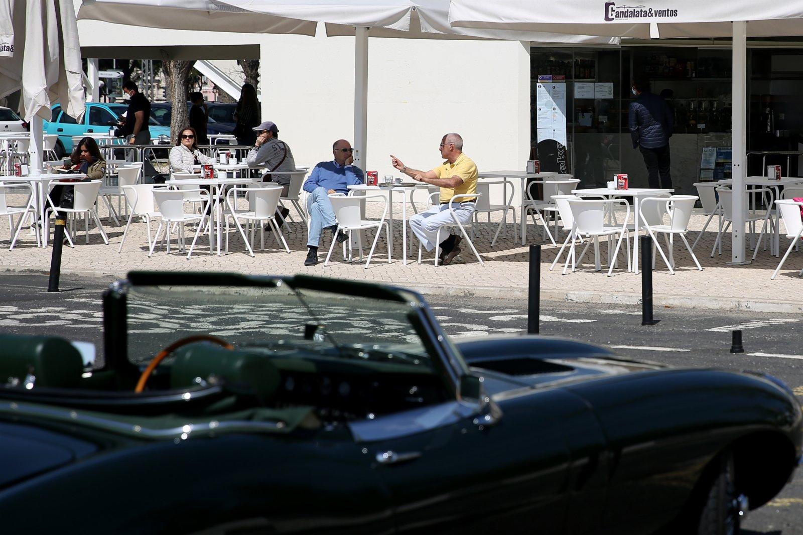人們在葡萄牙首都里斯本的咖啡廳戶外座位上喝咖啡聊天。