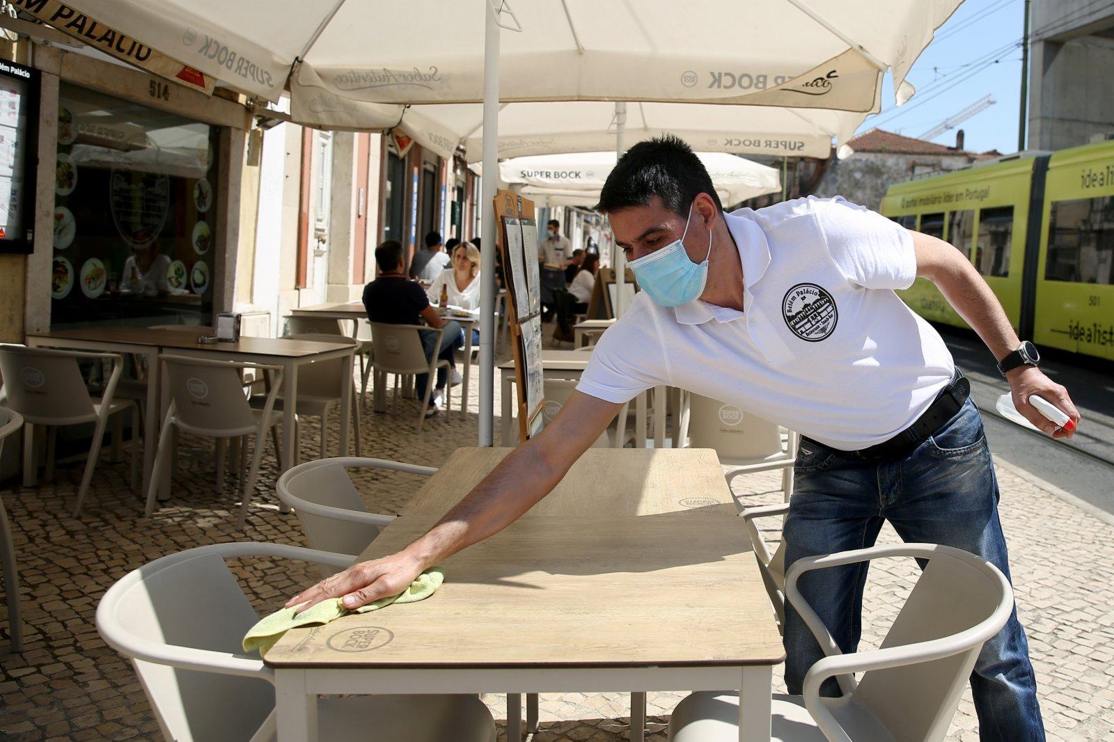 服務人員在葡萄牙首都里斯本擦拭消毒咖啡廳的戶外座位。
