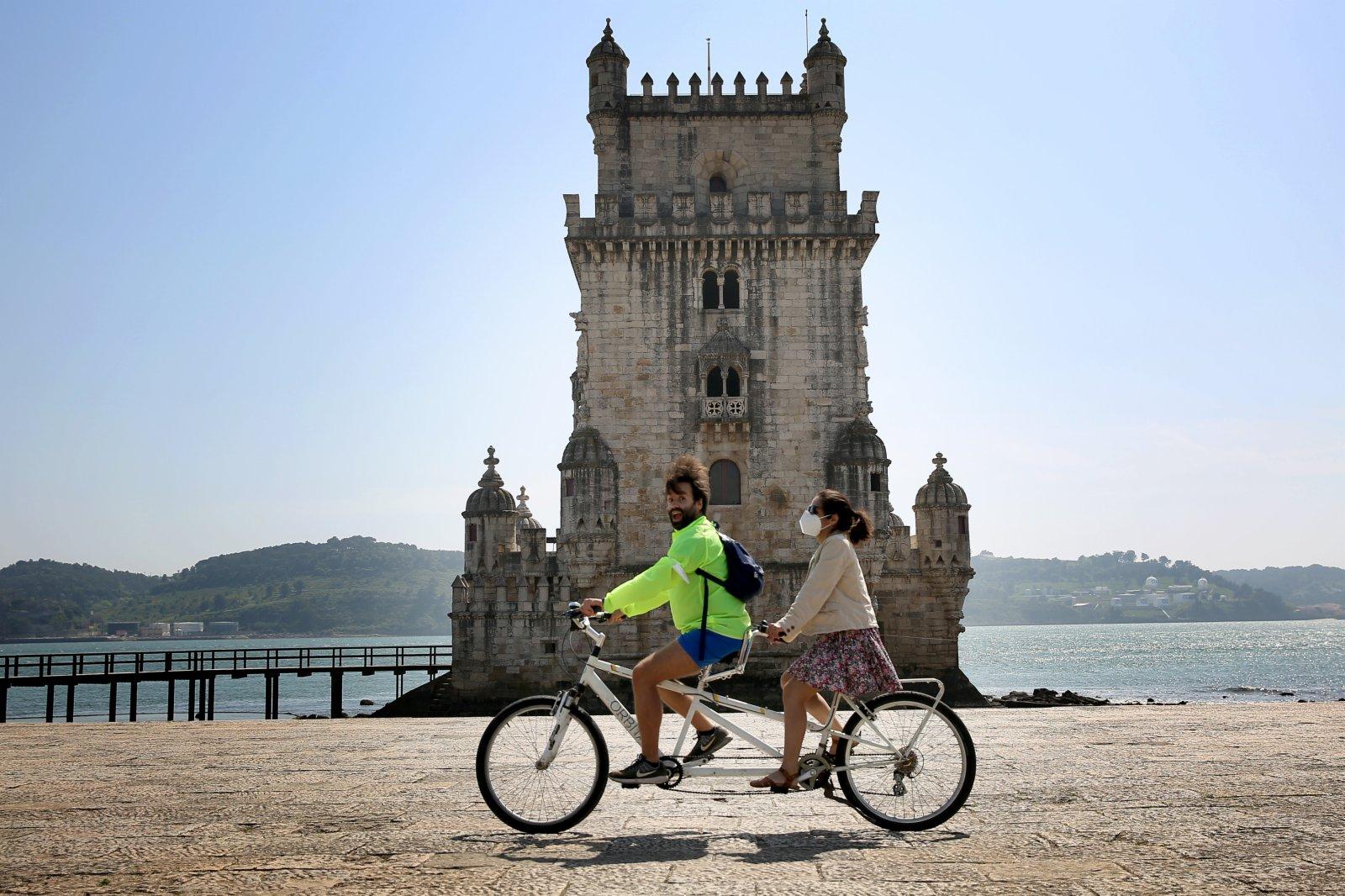 遊客在葡萄牙首都里斯本的貝倫塔騎車遊玩。