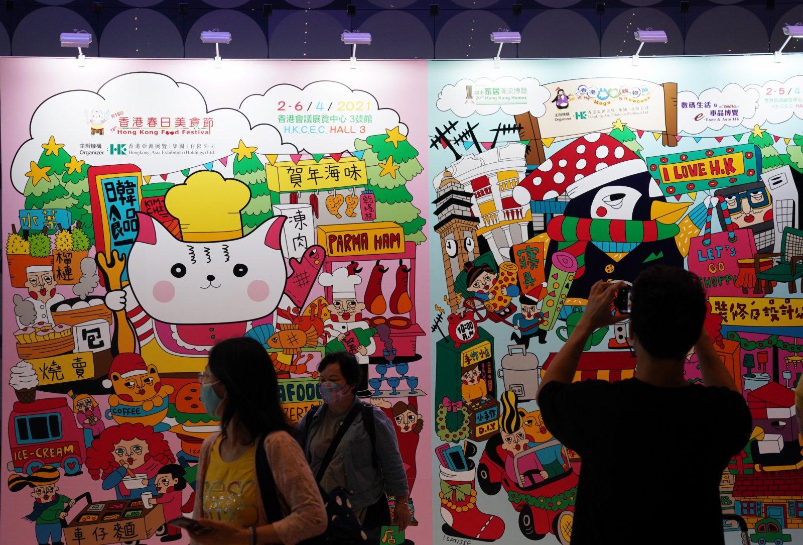 在香港會展中心舉行的「第十八屆香港春日美食節」上,參觀者在展板前拍照。