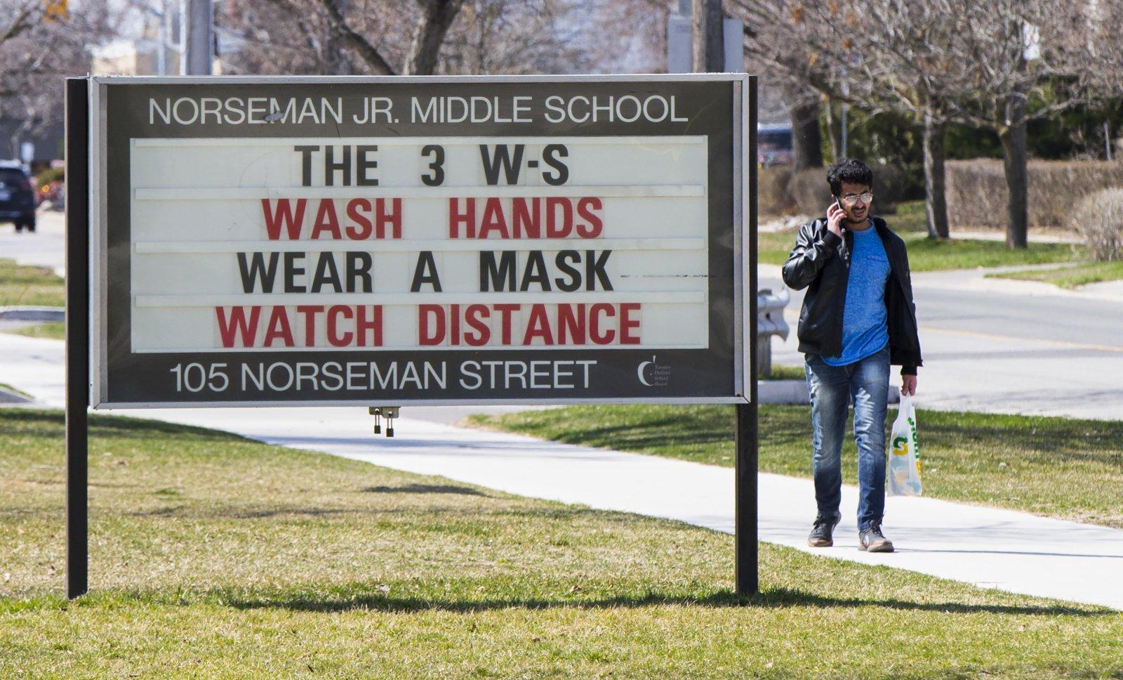 4月7日,一名男子從加拿大多倫多一所學校外的信息公告欄旁經過。(新華社)