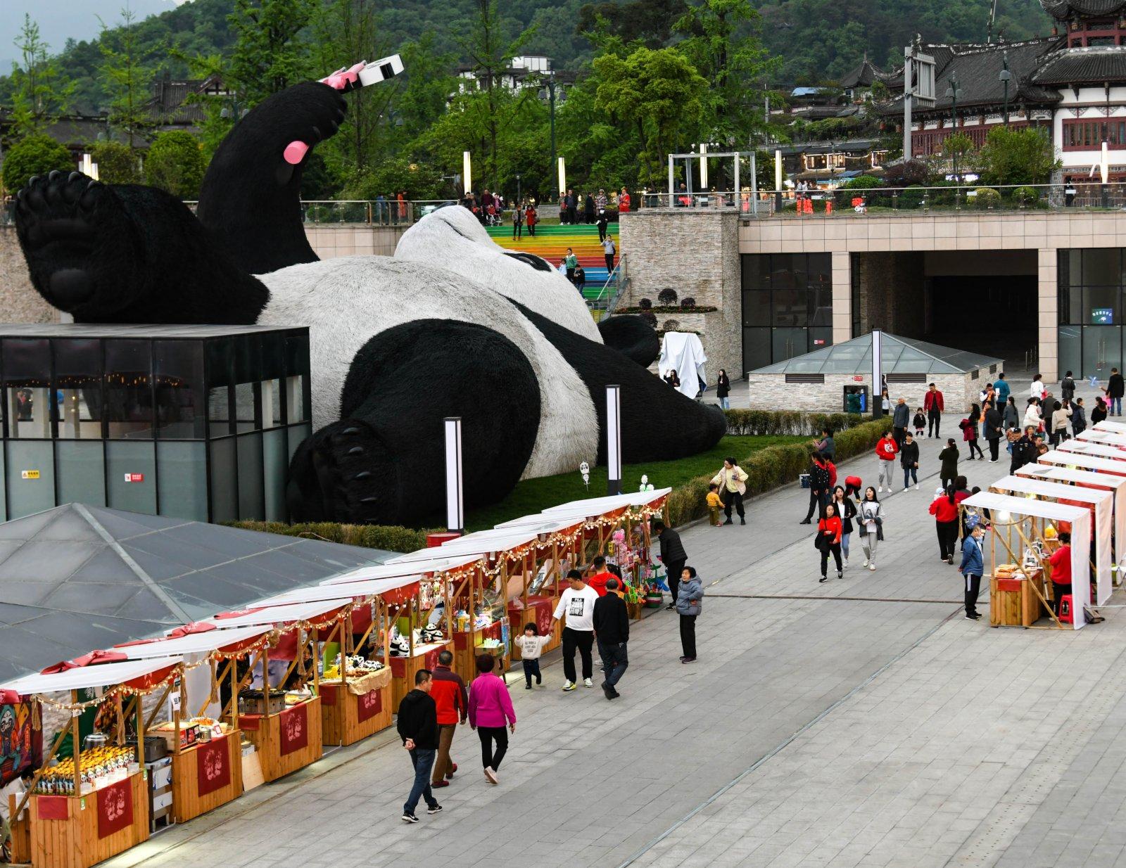 4月7日,在四川省都江堰市仰天窩廣場,遊客在「自拍熊貓」雕塑旁邊的文創集市消費。(新華社)