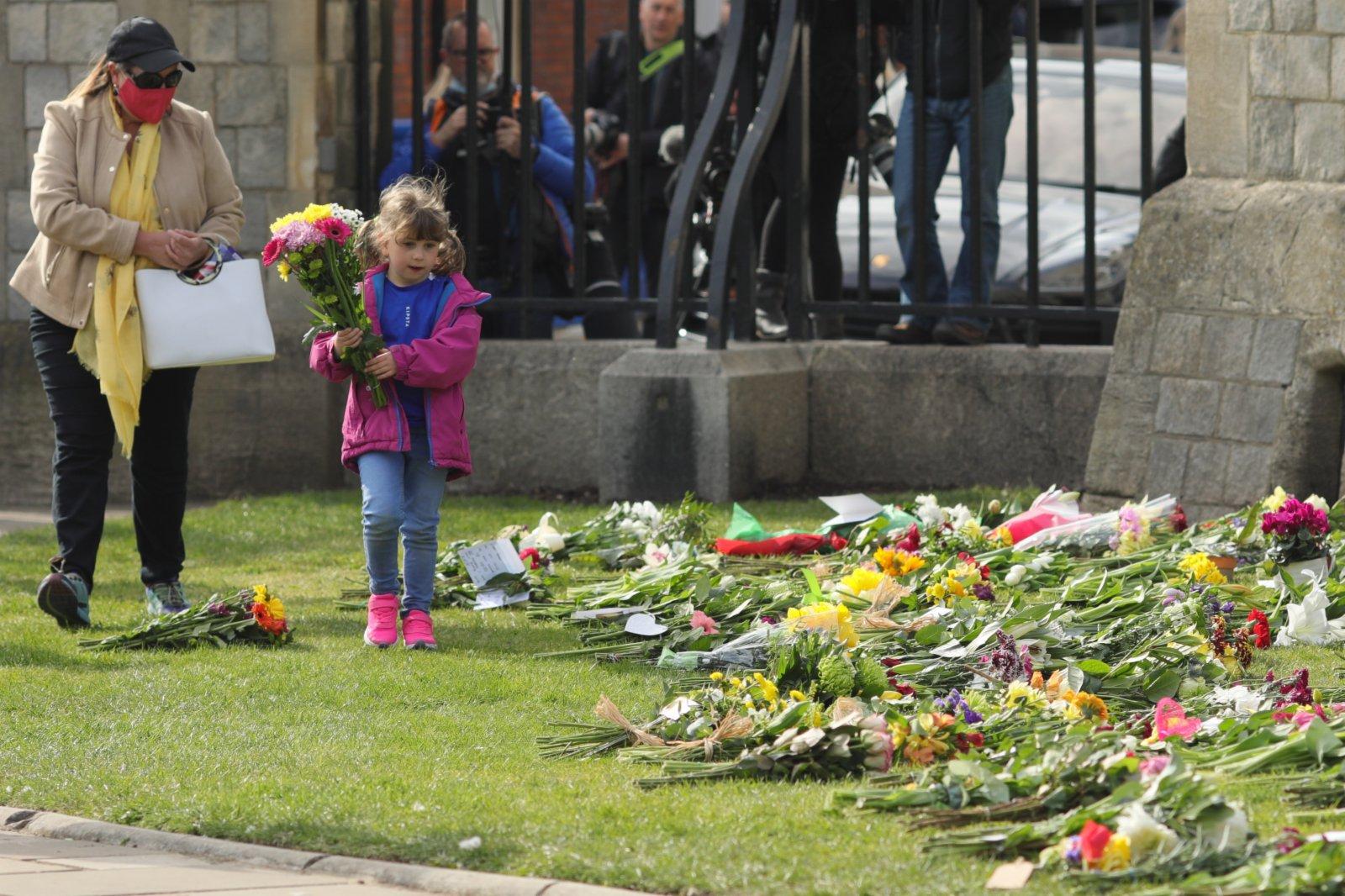 4月9日,一名小女孩準備在英國溫莎城堡前擺放鮮花。新華社