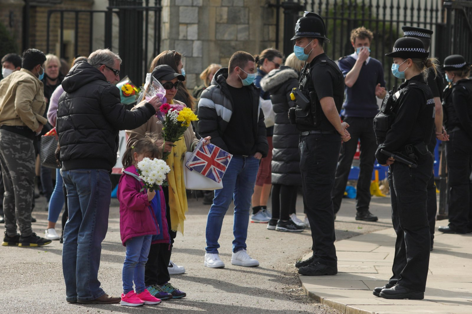 4月9日,人們手拿鮮花準備在英國溫莎城堡前擺放。新華社