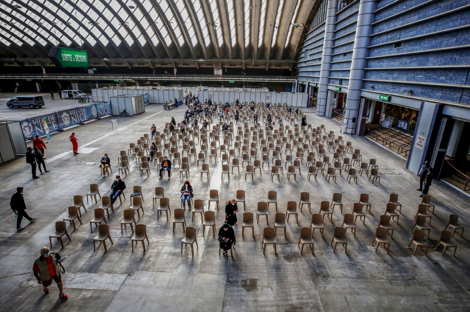 4月10日,人們在法國尼斯一家展覽中心設立的新冠疫苗接種中心等待接種疫苗。(新華社)