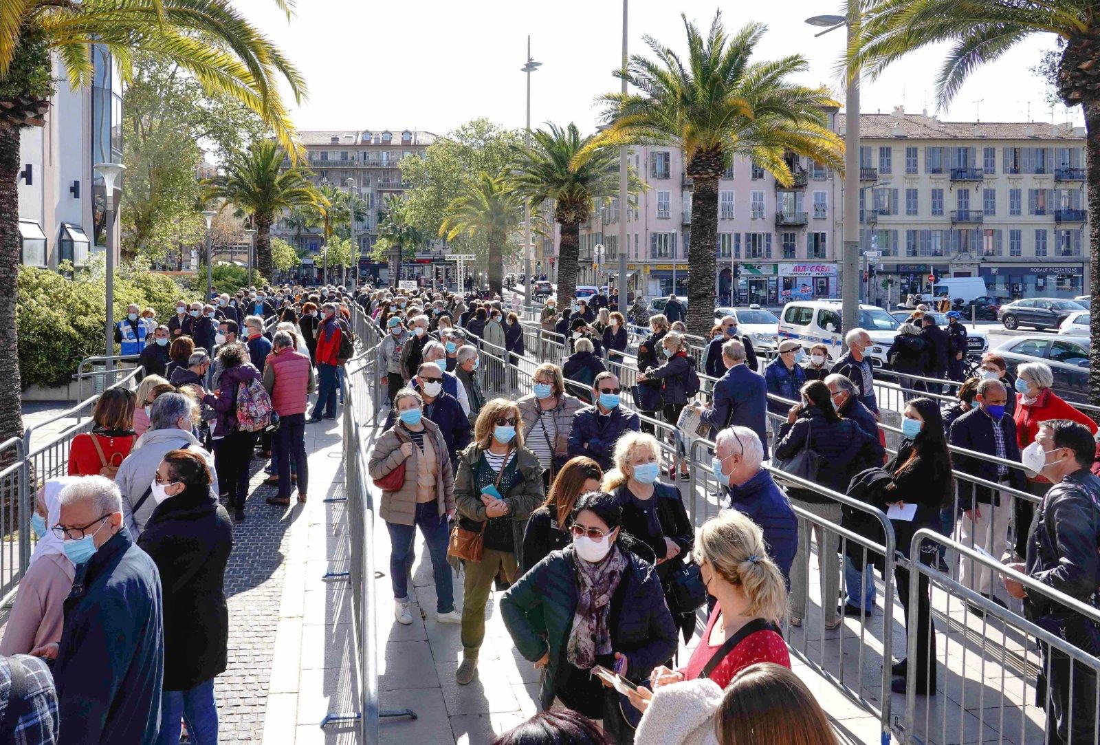 4月10日,人們在法國尼斯一家展覽中心設立的新冠疫苗接種中心排隊等待接種疫苗。(新華社)