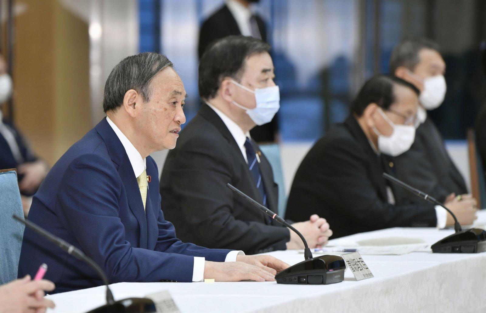 4月13日,在日本東京,日本首相菅義偉(左一)出席內閣會議。(新華社)