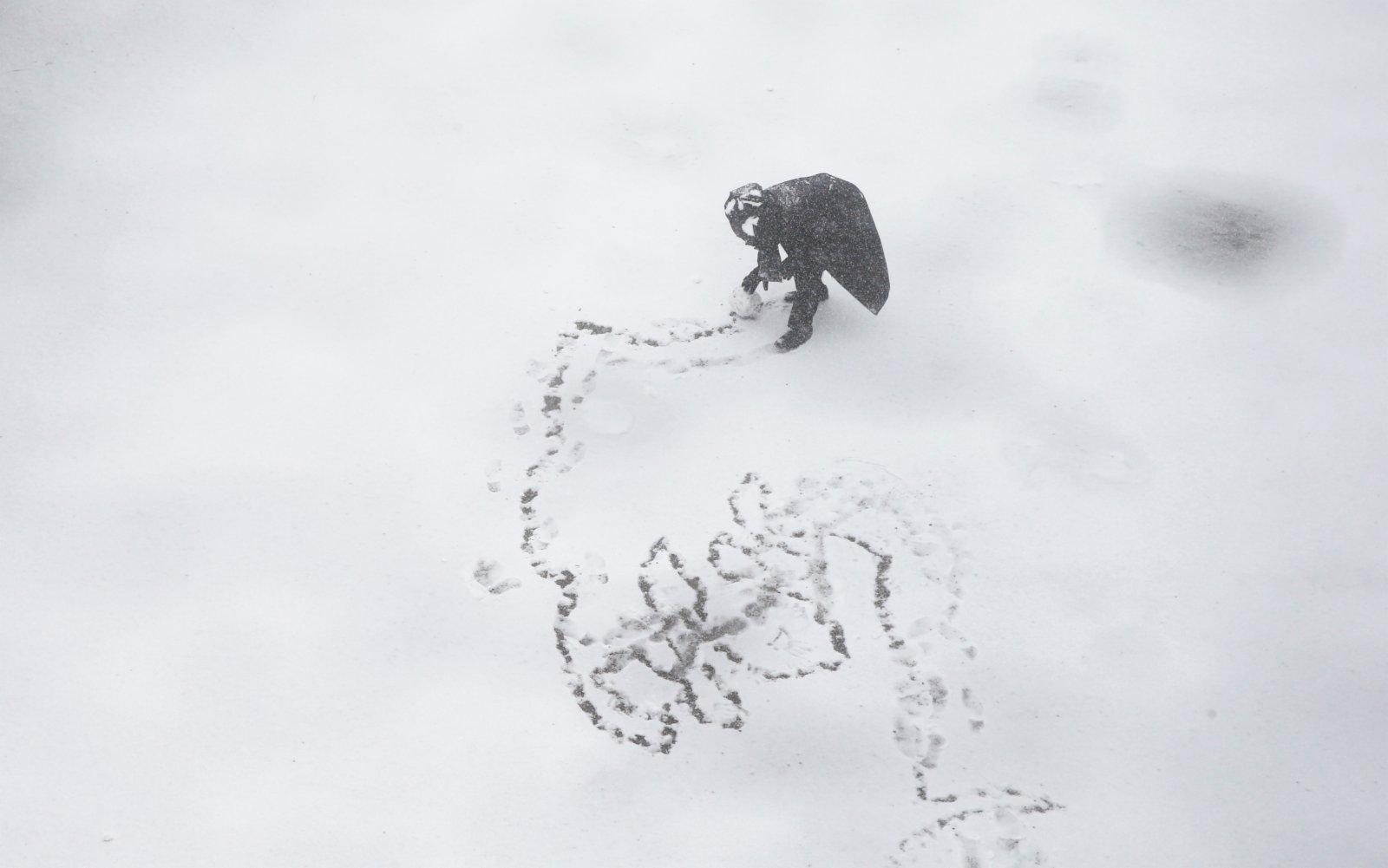 圖為一名男子在室外滾雪球。(路透社)