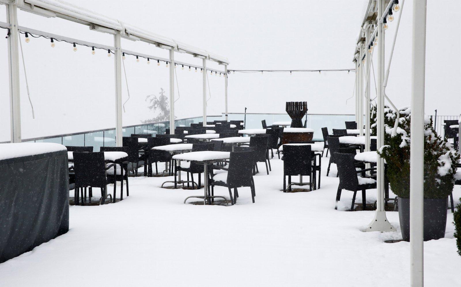 圖為一家餐廳露台上的椅子和桌子上積雪覆蓋。(路透社)