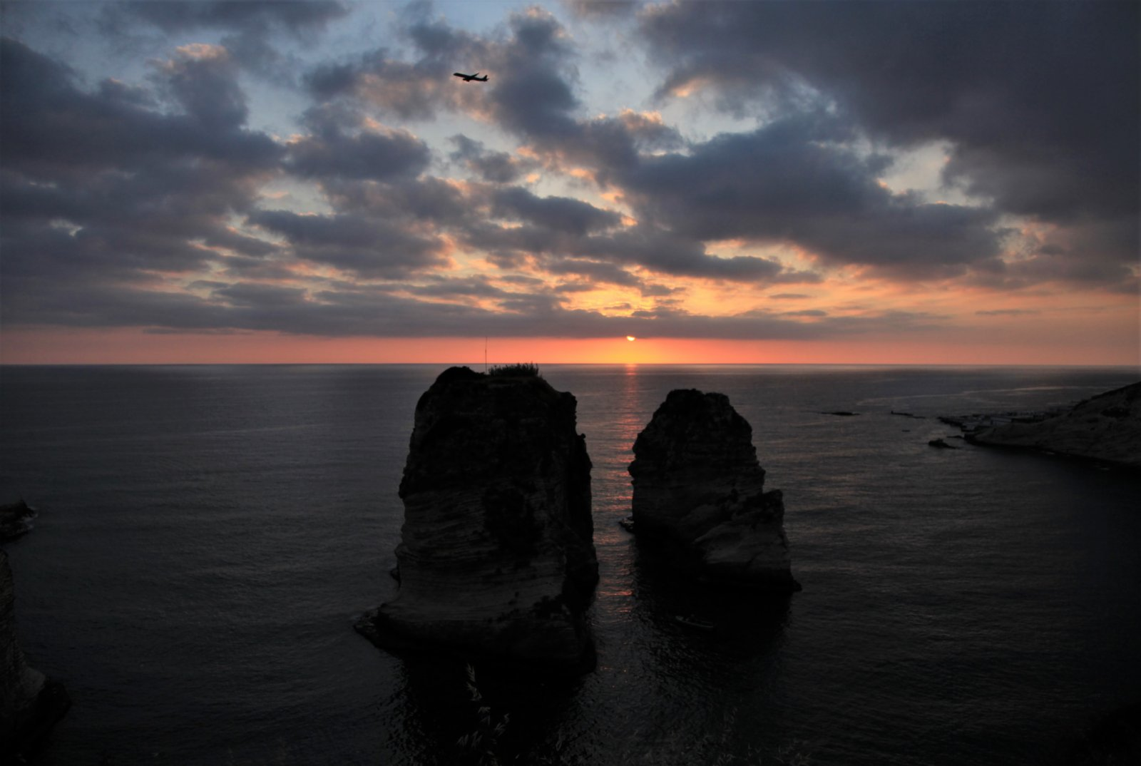 5月13日日落時分,一架飛機從黎巴嫩貝魯特著名景點鴿子岩上空飛過。(新華社)