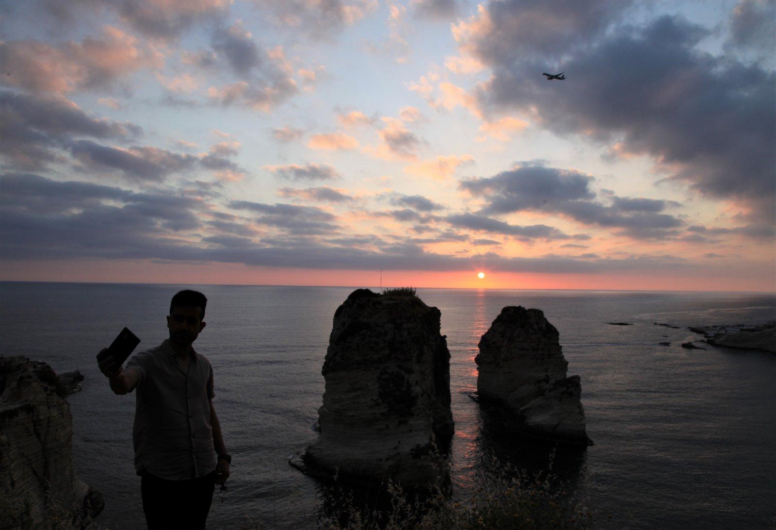 5月13日日落時分,一名男子在黎巴嫩貝魯特著名景點鴿子岩自拍。(新華社)