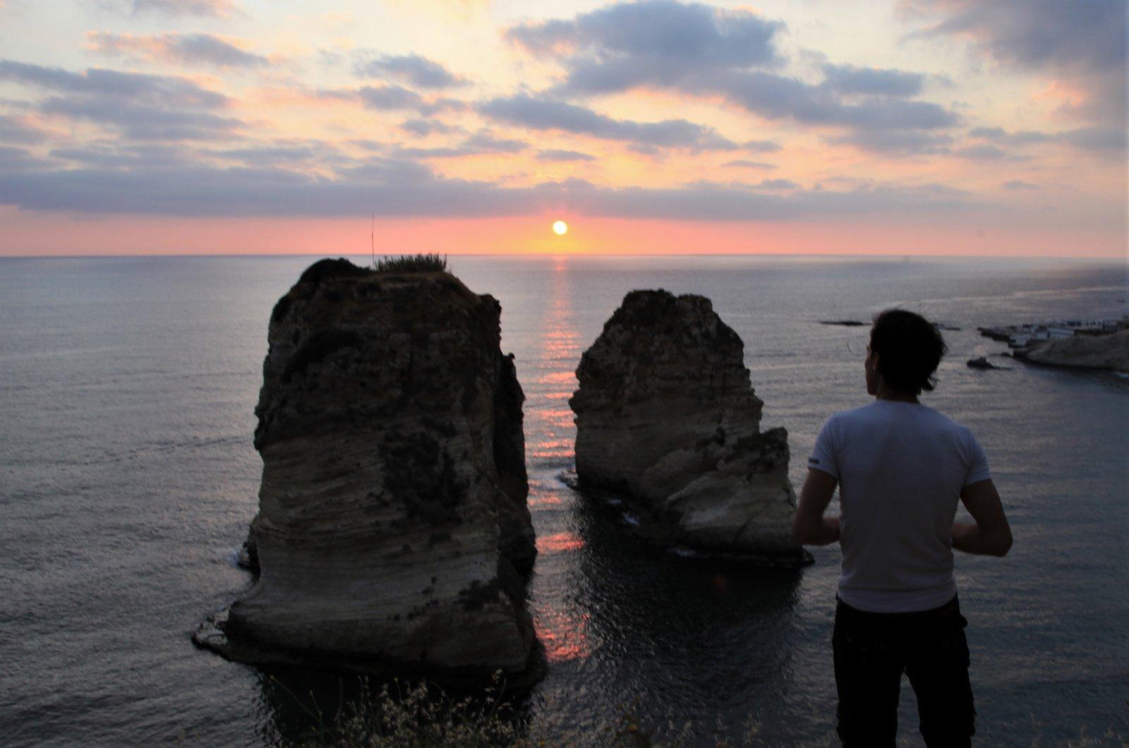 5月13日日落時分,一名男子在黎巴嫩貝魯特著名景點鴿子岩欣賞日落。(新華社)