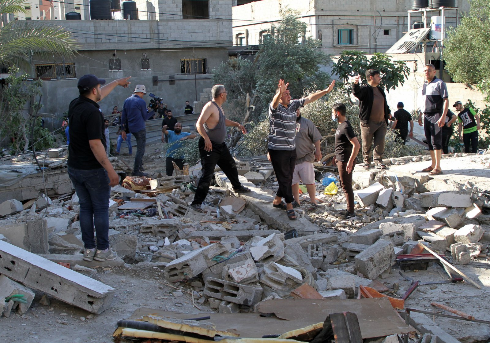 5月13日,人們在加沙地帶中部布賴傑難民營查看遭以軍空襲後的廢墟。(新華社)