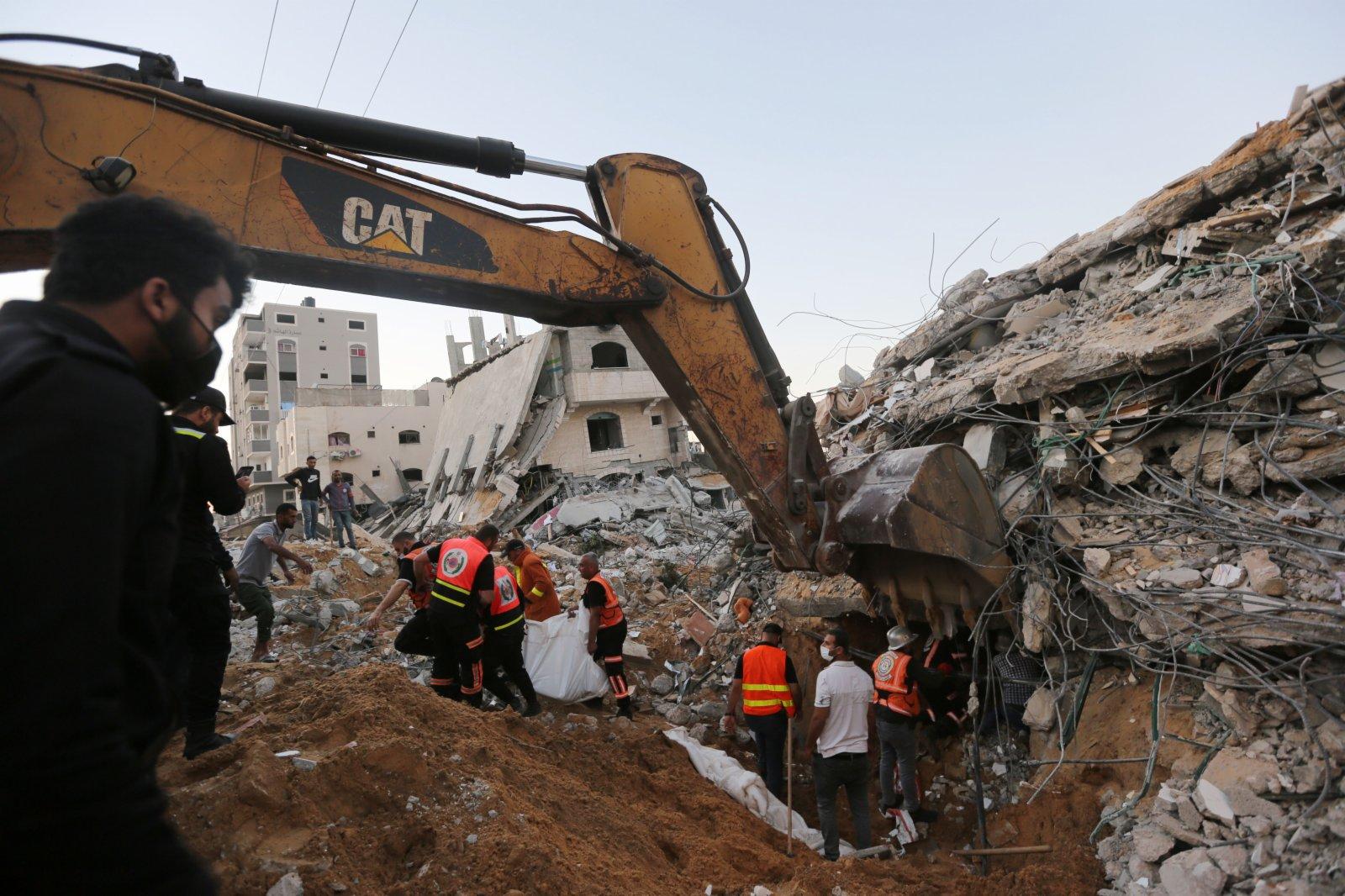 5月13日,救援人員在加沙地帶城鎮拜特拉希亞遭以軍空襲的廢墟中搜救。(新華社)