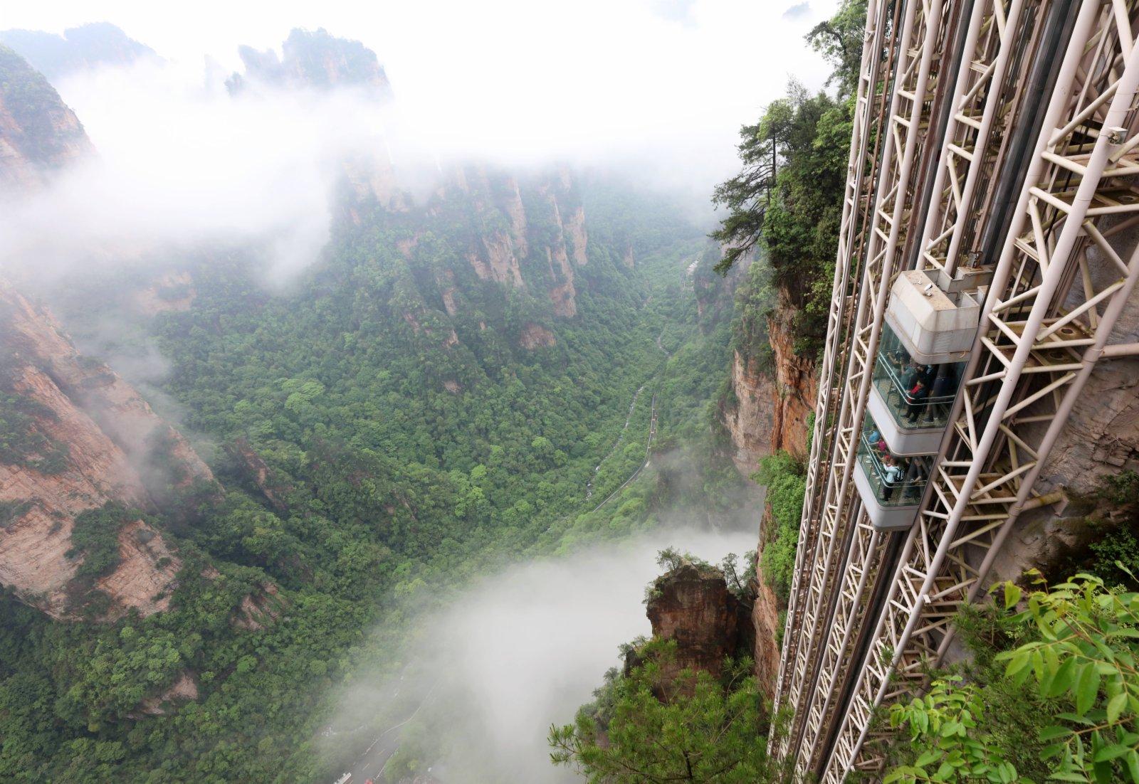 5月14日,遊人乘百龍天梯在雲霧繚繞的張家界武陵源景區遊覽。